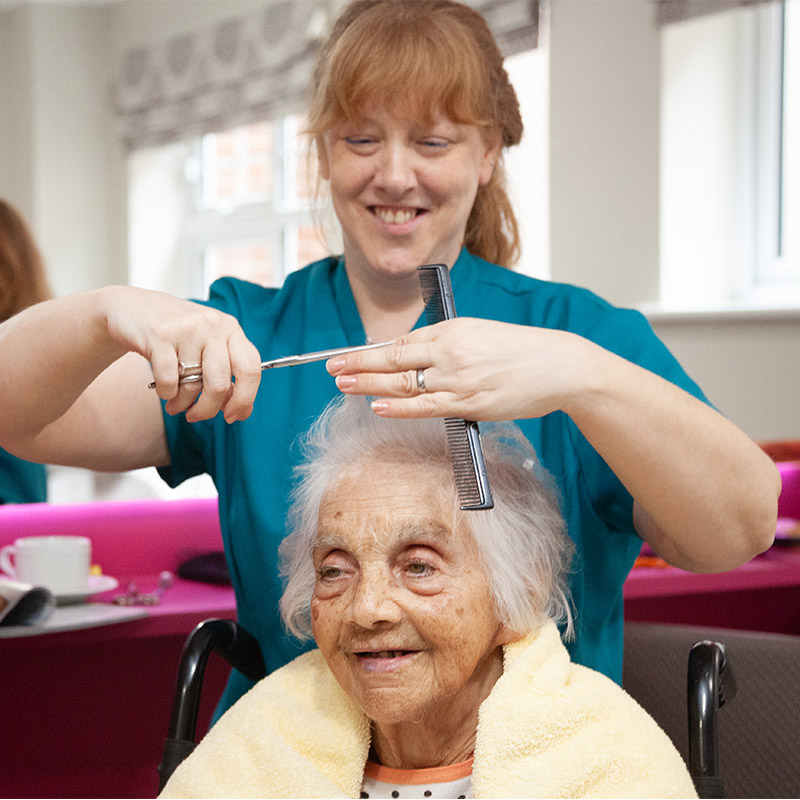 Care worker cutting hair of resident at care home